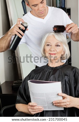 Female client with magazine while male hairstylist setting up her hair at salon - stock photo