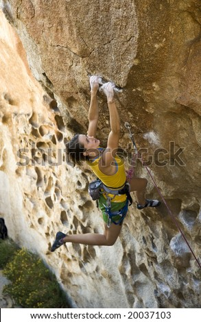 Female climber ascending an overhanging rock face in Joshua Tree National Park. - stock photo