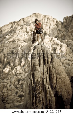 Female climber on the summit of a rock spire after a successful ascent, in Joshua Tree National Park, California. - stock photo