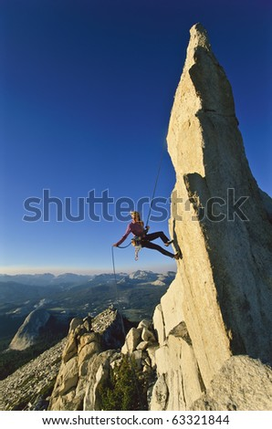 Female climber rappelling from the summit of an overhanging rock spire.