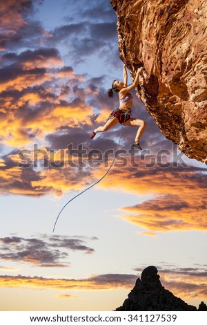 Female climber struggeling up a sheer cliff. - stock photo