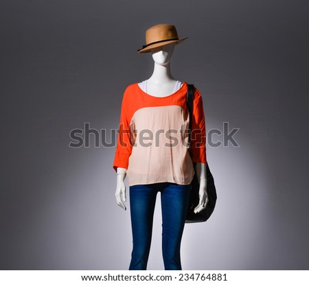 female clothing in jeans with hat ,bag on mannequin on gray background - stock photo