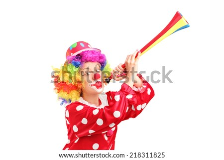 Female clown blowing a horn isolated against white background - stock photo