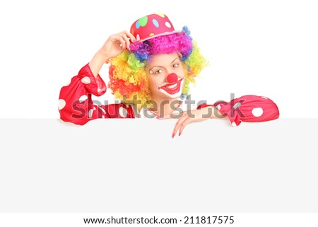 Female clown standing behind a blank panel isolated on white background - stock photo