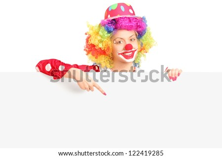Female clown with happy joyful expression pointing with finger on a blank panel isolated on white background - stock photo