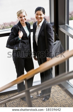 Female co-workers posing together in corner of office building - stock photo