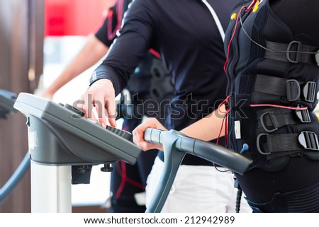 Female coach giving man and woman ems electro muscular stimulation ...