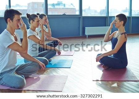 Female coach teaching young people how to do yoga exercises - stock photo