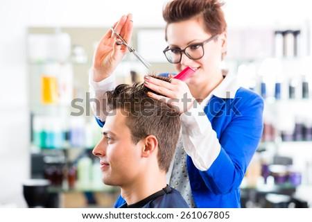 Female coiffeur cutting men hair in hairdresser shop - stock photo