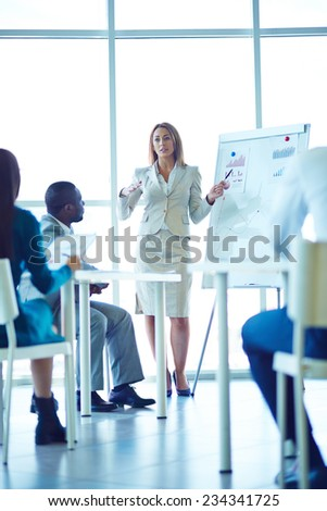 Female colleague delivering report to her colleagues - stock photo