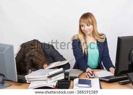 Female colleagues in the office, one had fallen asleep on a pile of folders, and the second looked at her - stock photo
