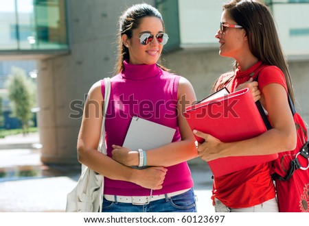 Female college friends talking on campus - stock photo