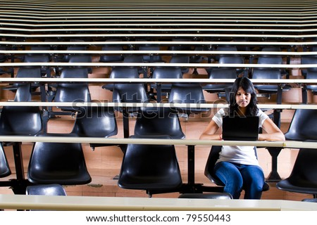 female college student alone in university lecture hall - stock photo
