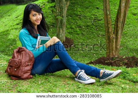 Female College student holding education books and posing