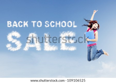 Female college student jumps on the side of clouds spelling out back to school sale - stock photo