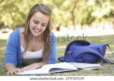 Female College Student Lying In Park Reading Textbook - stock photo