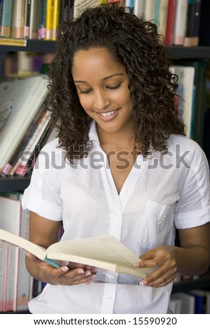 Female college student reading in a library