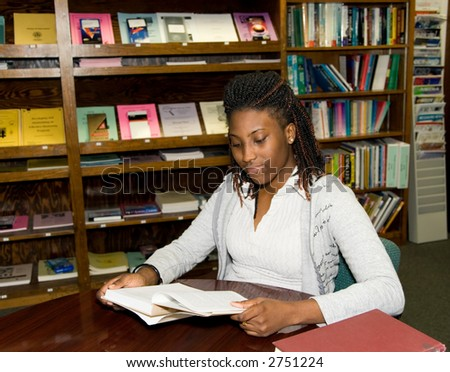female college student reading in the library - stock photo