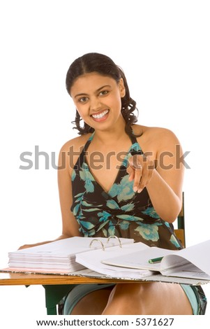 Female college student sitting by desk and pointing finger to viewer