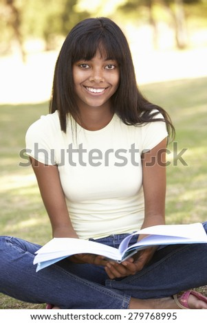 Female College Student Sitting In Park Reading Textbook - stock photo