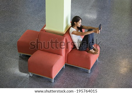 Female college student sitting on a plush chair in student commons lounge using her tablet
