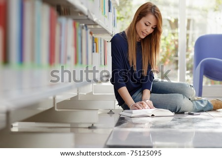 female college student sitting on floor in library, reading book and taking notes. Horizontal shape, full length, side view - stock photo