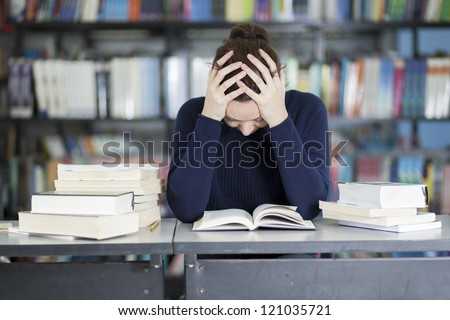 Female college student stressed about her homework - stock photo