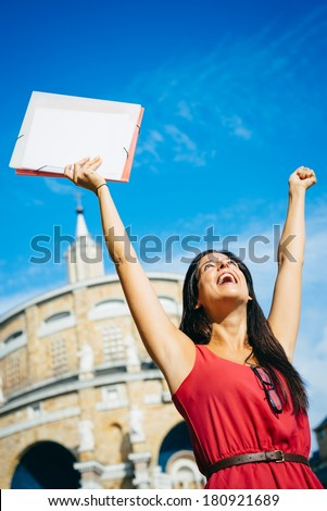Female college student success. Young blissful woman raising arms at college outdoor. Successful happy girl. - stock photo
