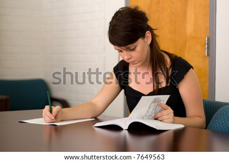 female college student uses the university catalogue to plan semester class schedule - stock photo