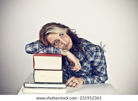 Female college student with a pile of heavy books - stock photo