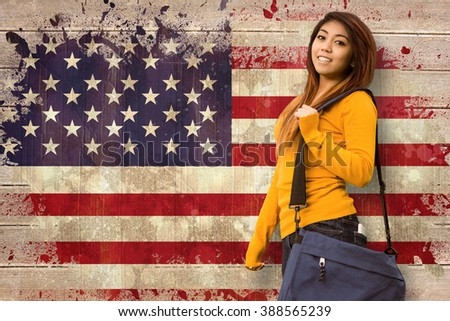 Female college student with bag in park against usa flag in grunge effect - stock photo