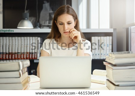 Female college student with long hair studying in the university library or study room, using notebook with copy space for your advertising content, looking at the screen with serious expression