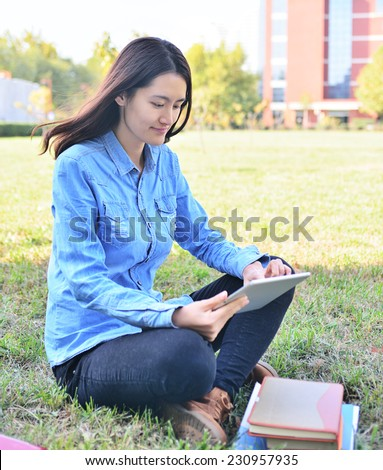 female college student with Tablet PCs on campus - stock photo