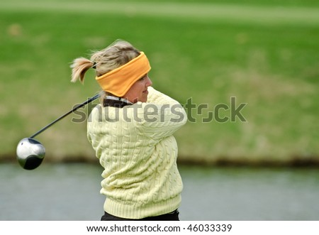 Female collegiate golfer captured in her follow through swing with a driver. - stock photo