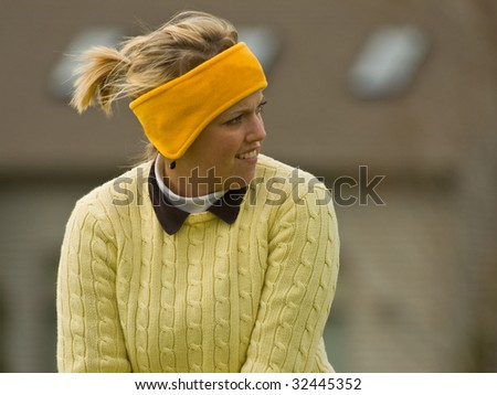 Female collegiate golfer positioned in golf stance preparing to drive the ball - stock photo