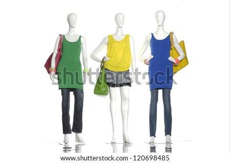 female colorful dress with bag on three mannequin - stock photo