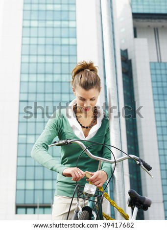 female commuter locking padlock to her bike. Copy space
