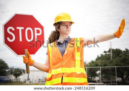 Female construction apprentice holding a stop sign and directing traffic.   - stock photo