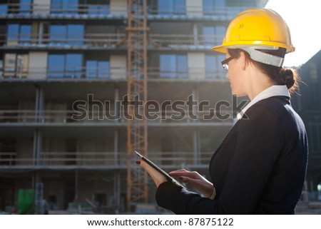 Female construction engineer/architect using tablet computer at construction site - stock photo