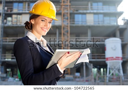 Female construction engineer / architect with a tablet computer at a construction site - stock photo