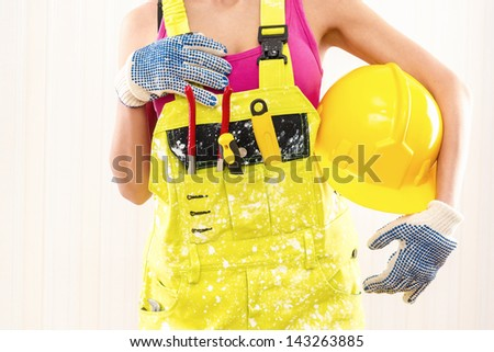 Female construction worker in coverall holding hardhat posing indoors - stock photo