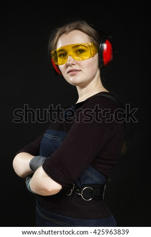 Female construction worker in protective headphones and level safety glasses. Photo on black background. - stock photo