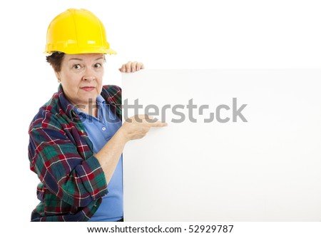 Female construction worker points at blank white space, ready for text.  Isolated on white.