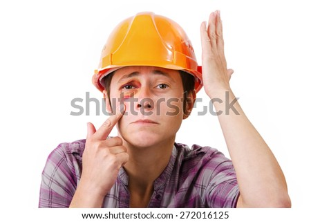 Female construction worker with a black eye in the helmet