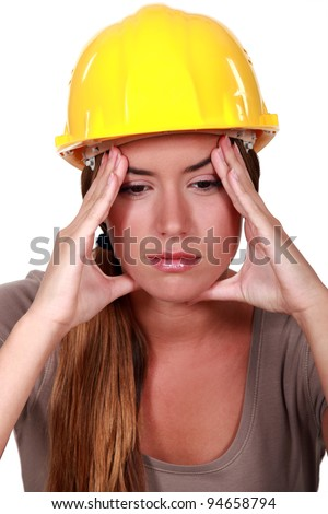 Female construction worker with a headache