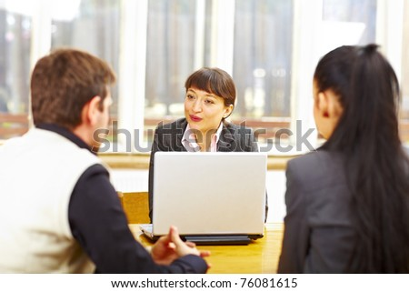 Female consultant advising couple sitting at the computer