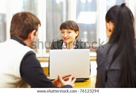 Female consultant advising couple sitting at the computer - stock photo