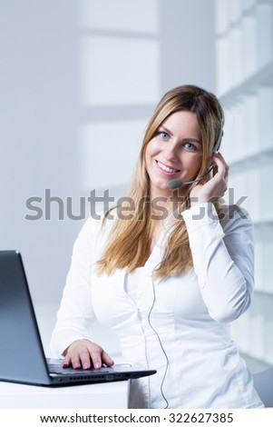 Female consultant with headset working in call center - stock photo