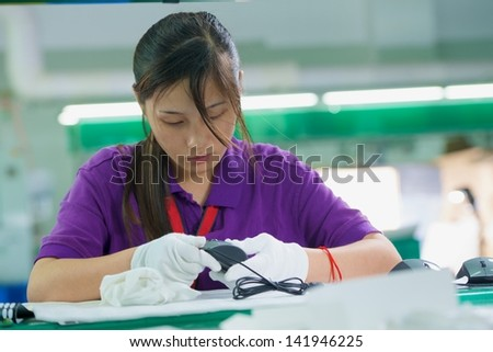Female conveyor worker in white gloves assembling electronic device on Chinese factory - stock photo