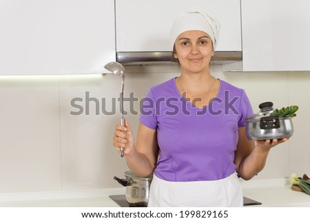 Female Cook in the kitchen smiling while holding pot and ladle - stock photo